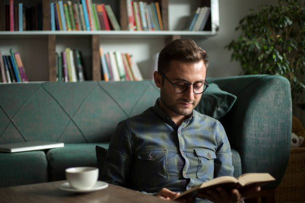 Young man reading a book at home stock photo