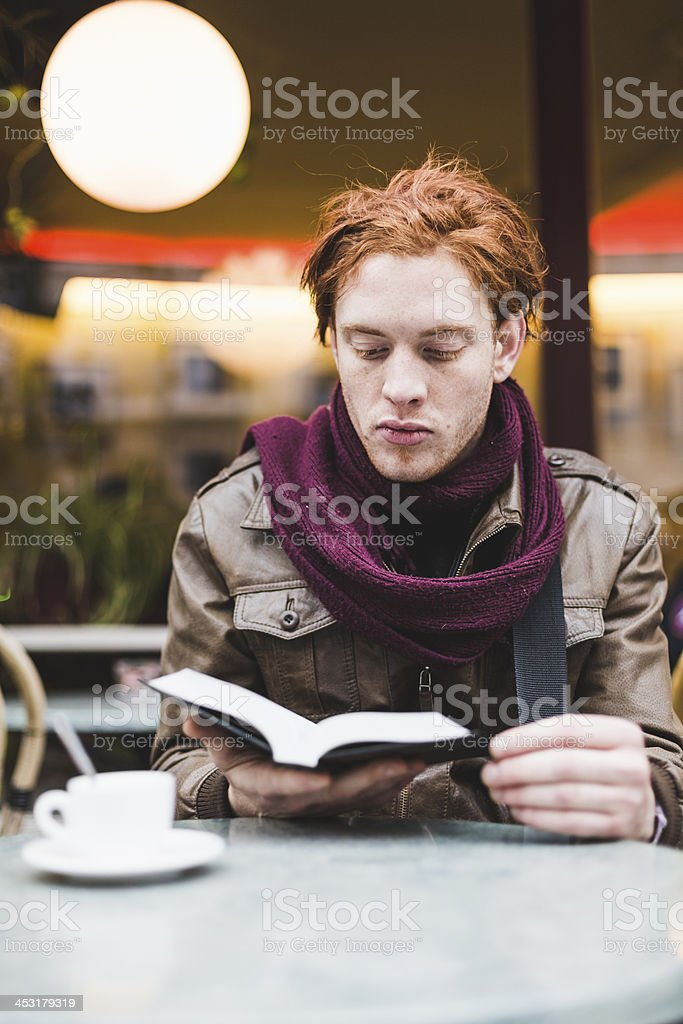 Young man reading a book at the bar stock photo
