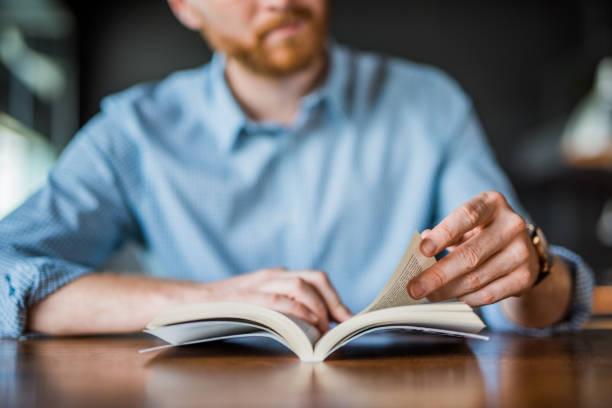 genç adam kitap el okuma yakın. - kitap stok fotoğraflar ve resimler