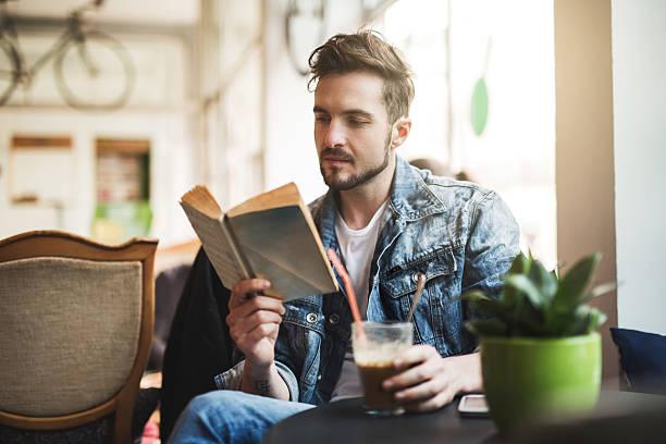 Junger Mann liest ein Buch in einem Café. – Foto