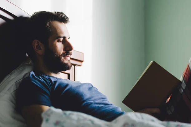 Young man reading a book in his bedroom stock photo