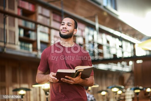 Young african-american student holding a book and standing in the middle of a public library.