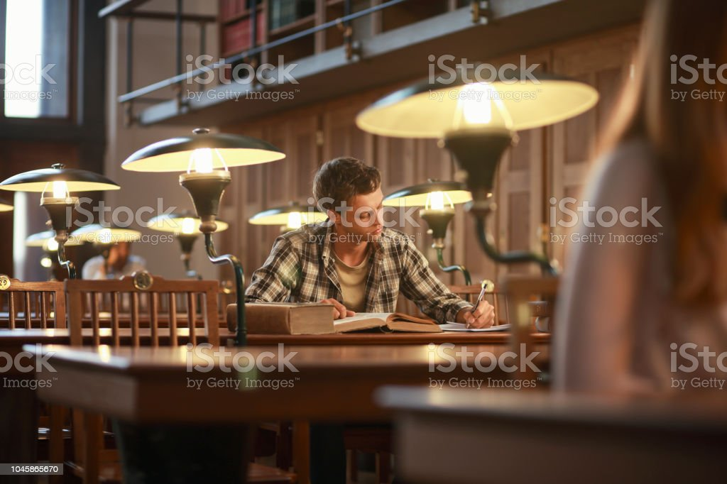 Young man reading a book in public library stock photo