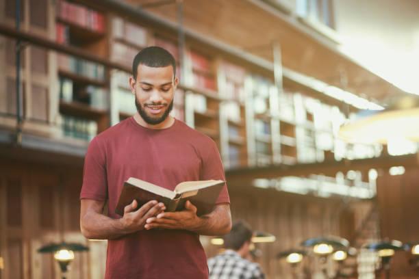 Junger Mann liest ein Buch in öffentlicher Bibliothek – Foto