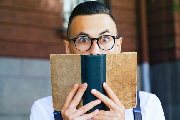Young man reading a book stock photo