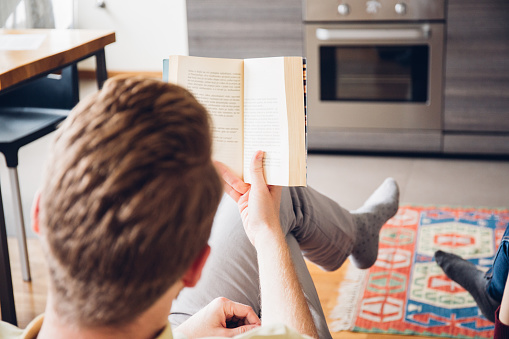 973962076 istock photo Young man reading a book 969445636