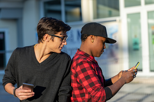 Young man reading a friends phone messages peering over his shoulder as they stand in an urban street using their smartphones
