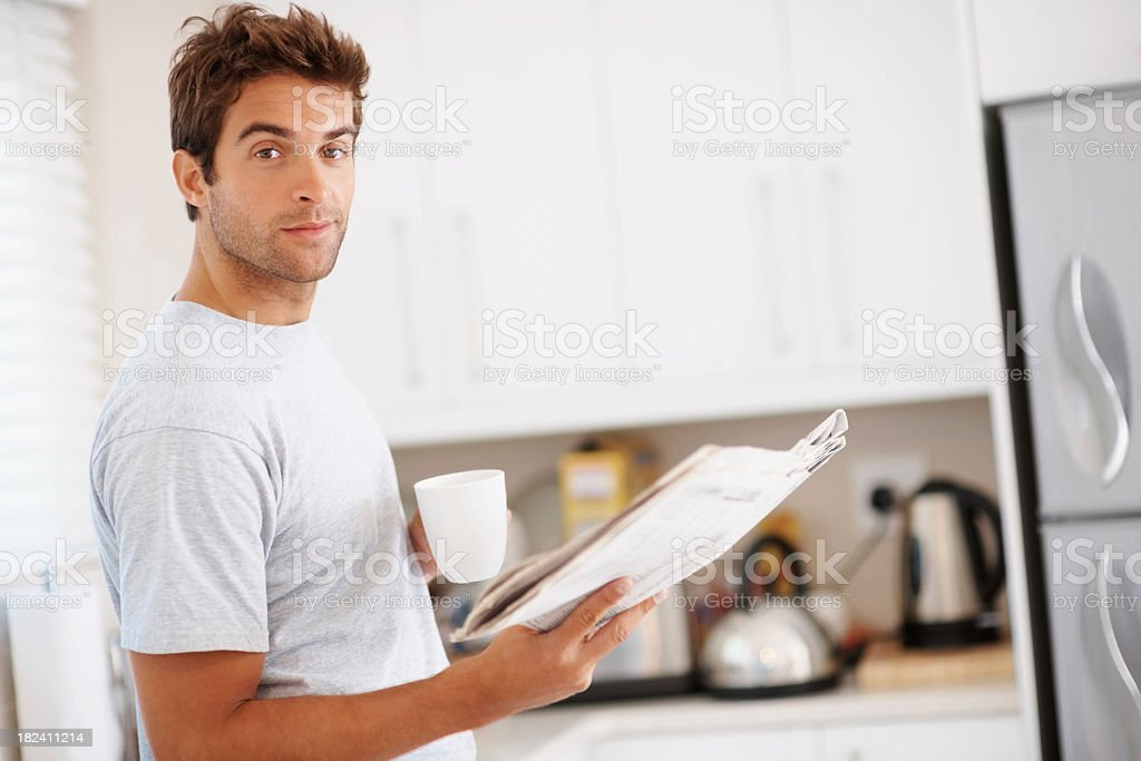Young man reading a newspaper in the kitchen royalty-free stock photo