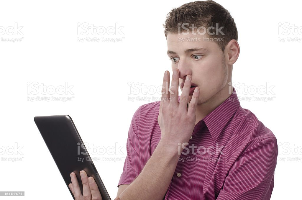 Young man reading a shocking news on the tablet. royalty-free stock photo