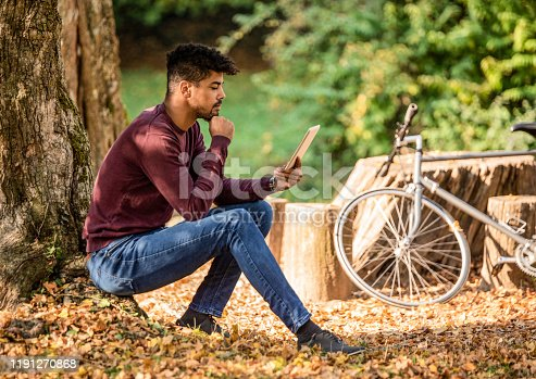 Young man reading an article on digital tablet in nature.