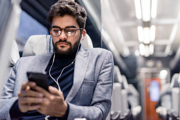 Young man reading an article on his phone and listening to podcasts while traveling by train. stock photo