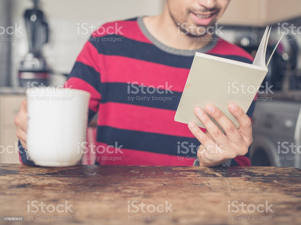 Young man reading and drinking coffee stock photo