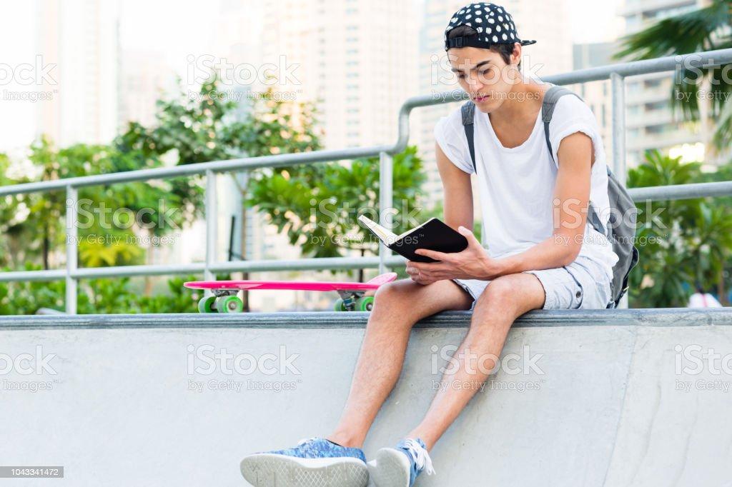 Jovem de leitura no parque de skate. - foto de acervo