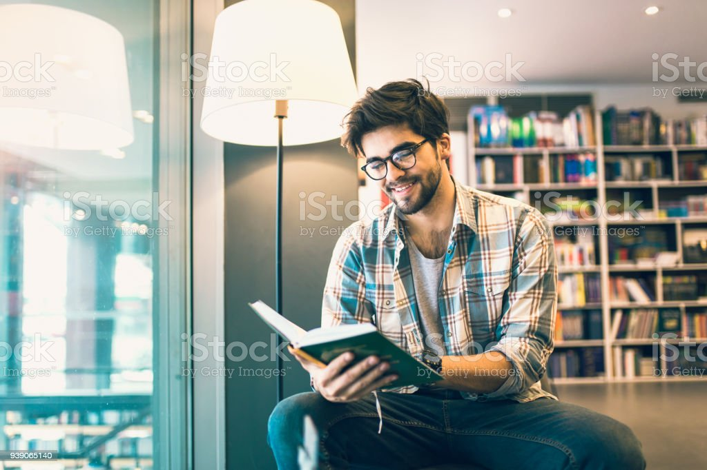 Young man reading book in the library stock photo