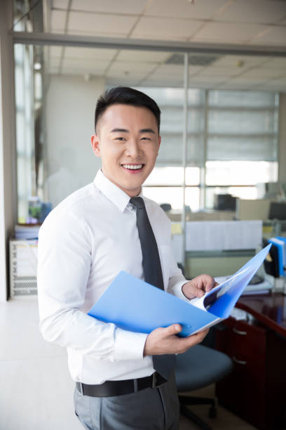 young man reading documents near by window young man wearing a suit, reading documents in the company, modern office civil servant stock pictures, royalty-free photos & images