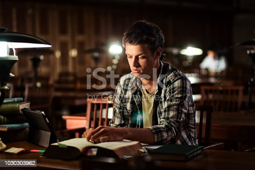 Young male reading an old book with an old electric lamp in a library's reading room at night.