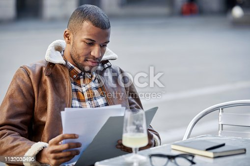 Young man reading papers. Male is sitting at table in sidewalk cafe. He is wearing casuals.