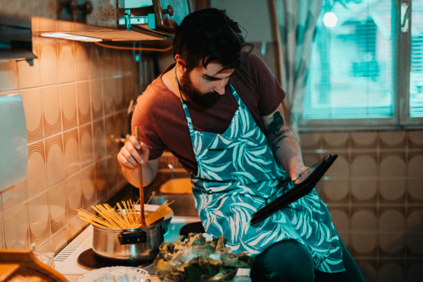Young man reading recipe on digital tablet and cooking stock photo