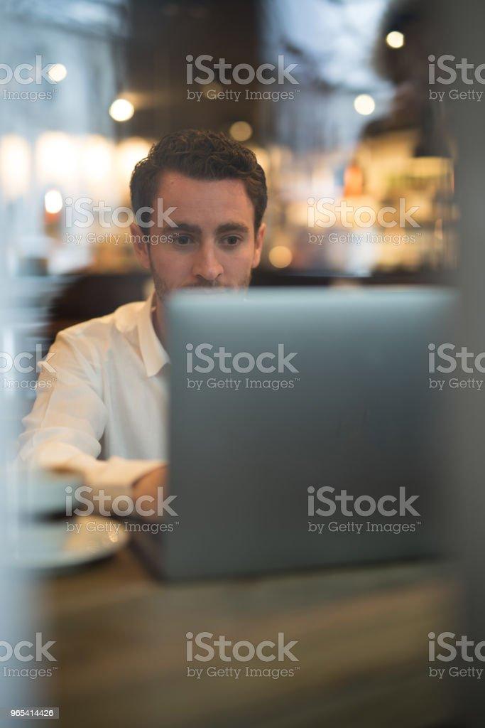 Young man reading something on laptop. zbiór zdjęć royalty-free