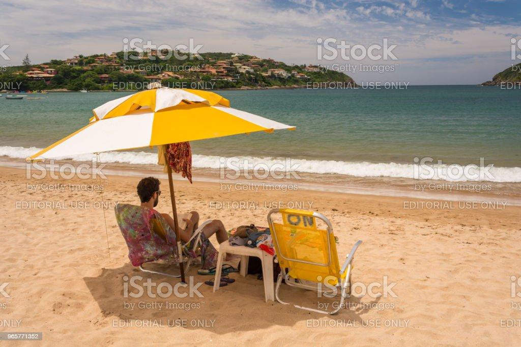 Young man reading under the shadow of a yellow umbrella, on Ferradura beach - Royalty-free Adult Stock Photo