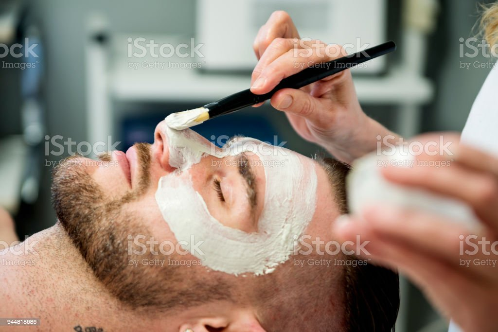 Young man receiving a facial treatment in beauty spa. stock photo