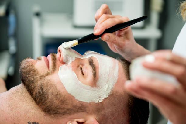 Junger Mann erhält eine Gesichtsbehandlung im Beauty Spa. – Foto