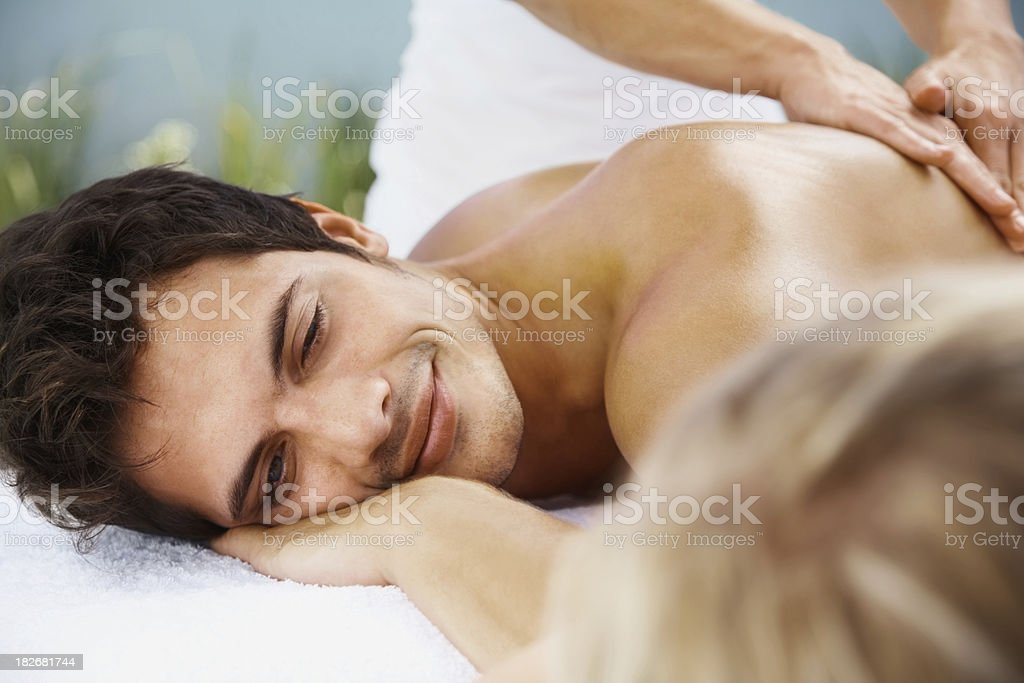 Young man receiving body massage while alongside a woman royalty-free stock photo