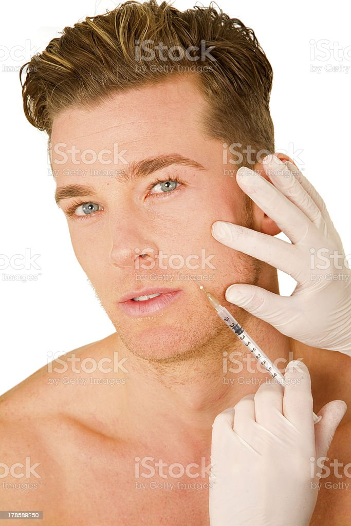 Young man receiving Botox injections in his upper lip stock photo