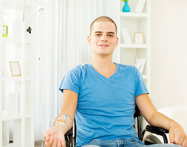 Young Man Receiving Chemotherapy at home. Portrait of an young man receiving chemotherapy at home. shaved head stock pictures, royalty-free photos & images