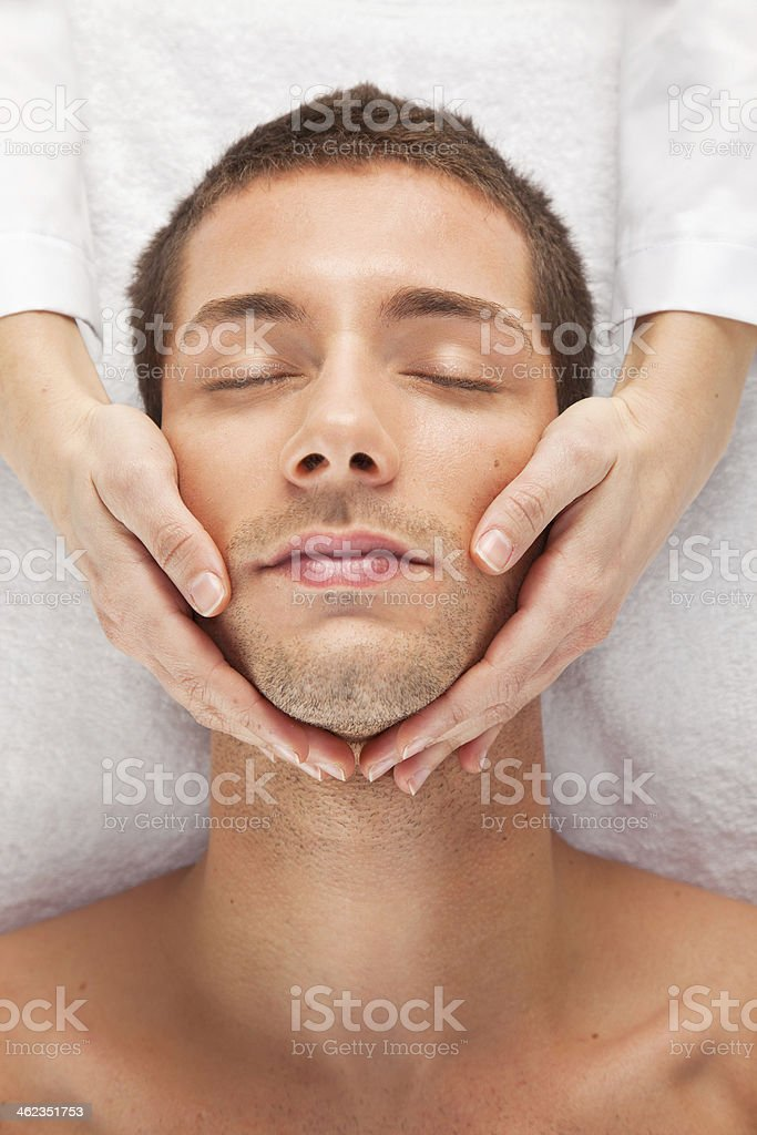 Young man receiving facial massage stock photo