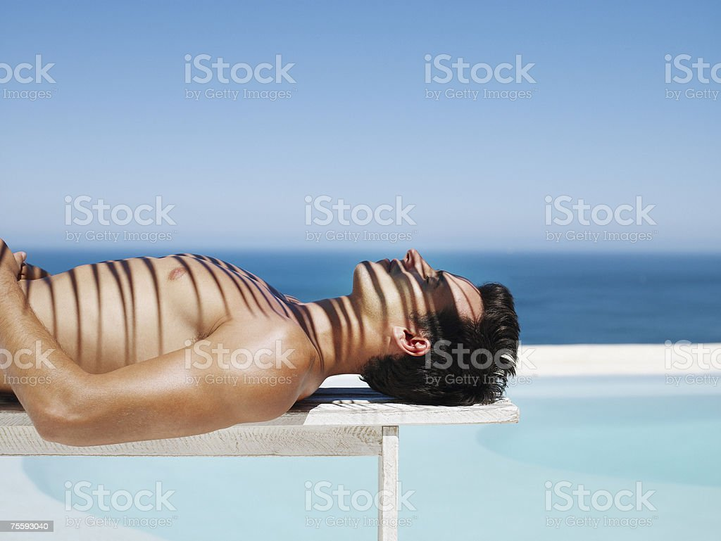 Young man reclining and lying in the sun royalty-free stock photo
