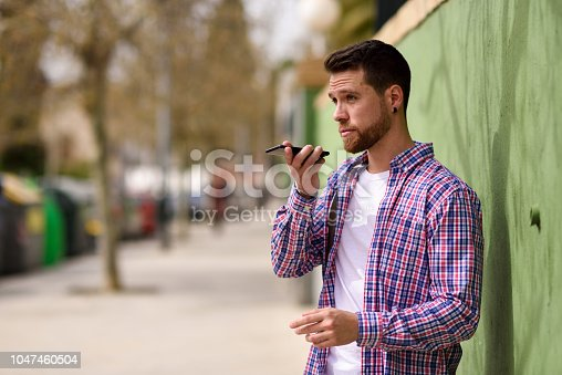 Young man recording voice note in his smart phone in urban background. Guy wearing casual clothes. Lifestyle concept.