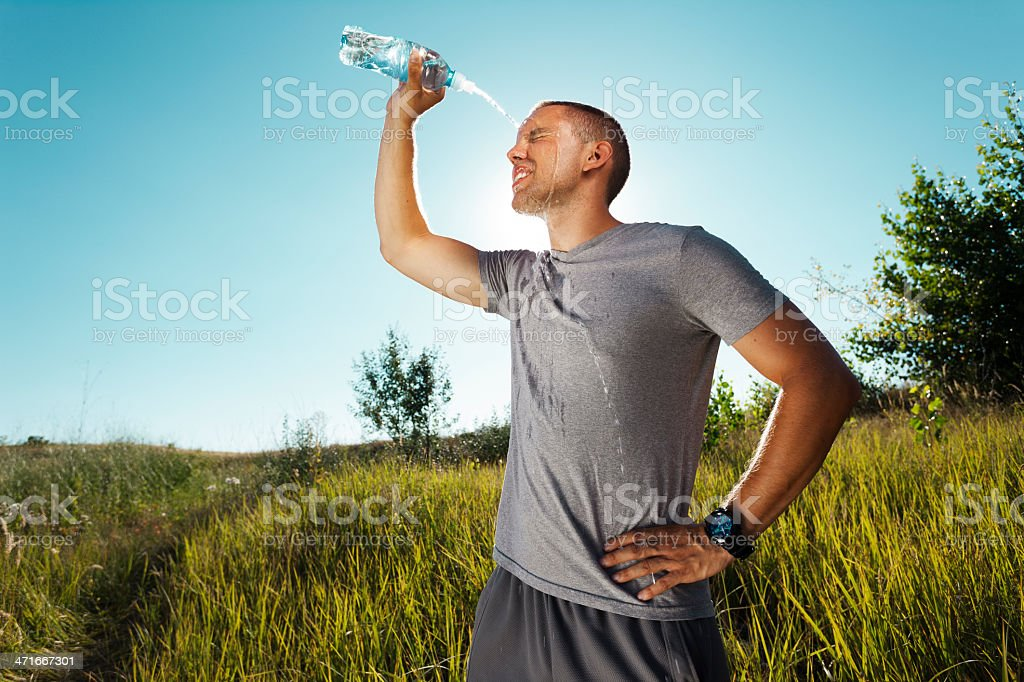 Young man refreshing himself with water stock photo