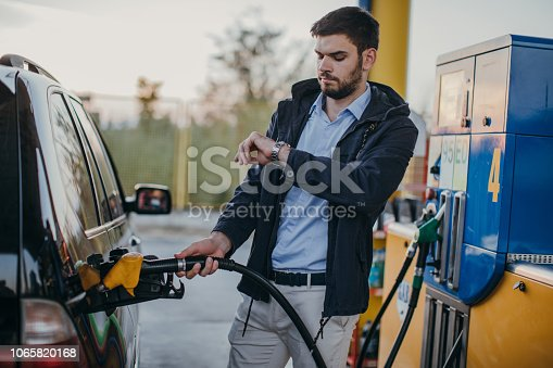 Young man refueling gas tank at the gas station