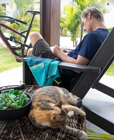 Young man relaxes with his cat in patio chair in the morning