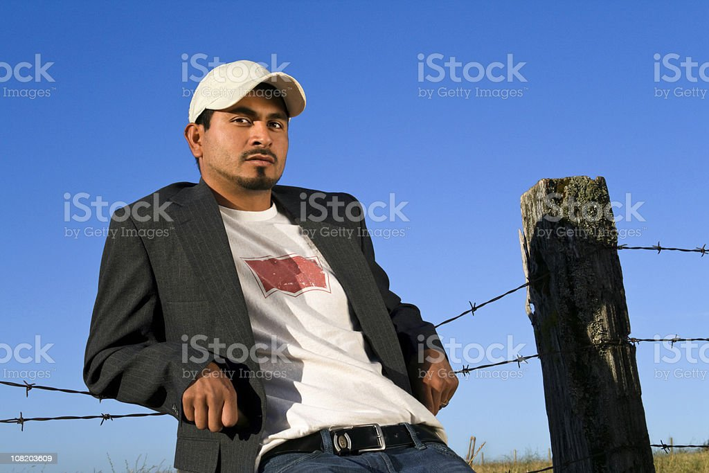 Young Man Relaxing Against Fence stock photo