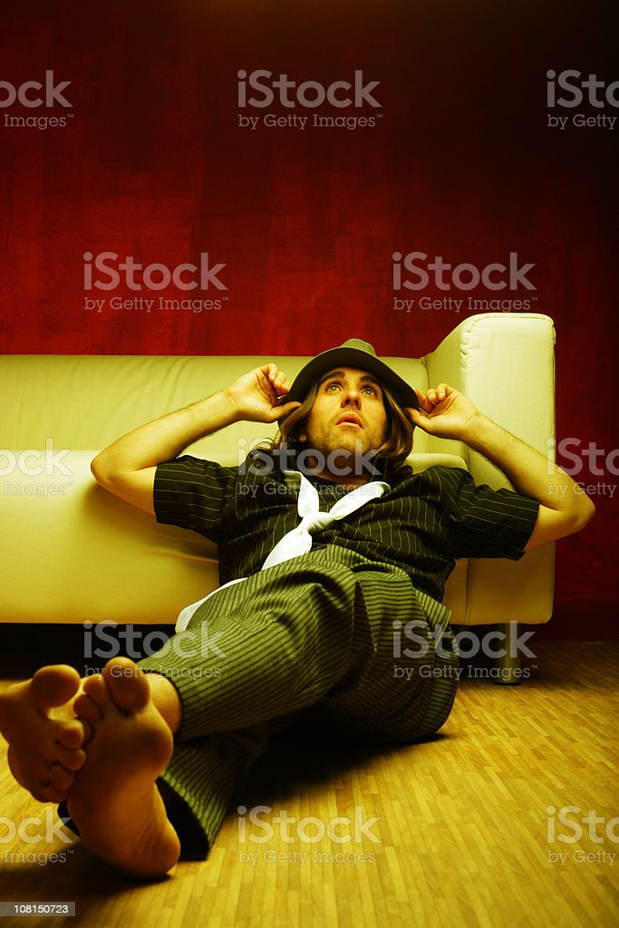 Young Man Relaxing and Leaning Against Couch royalty-free stock photo
