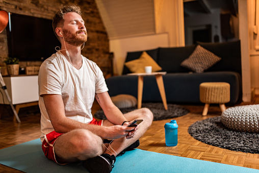 Young male athlete calming his mind with guided meditation on earphones at home.