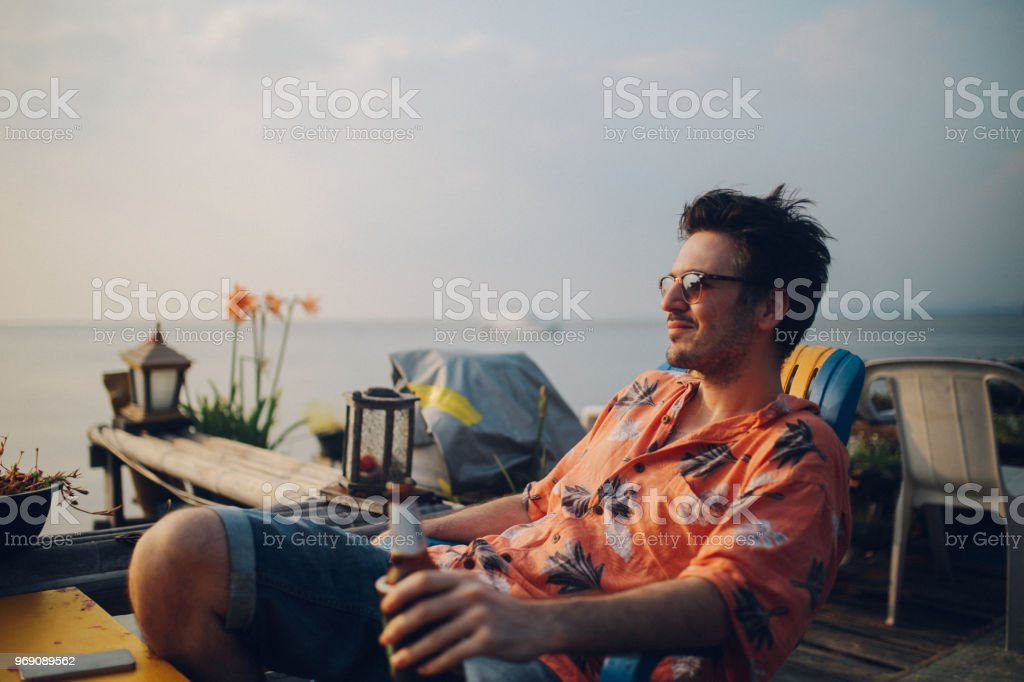 Young man relaxing by the ocean, having a beer, looking at sunset at Koh Lanta, Thailand stock photo