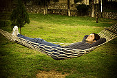 Young man relaxing on the hammock in a beautiful garden