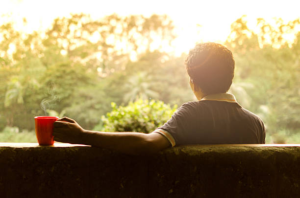 Young man relaxing in a garden holding coffee stock photo