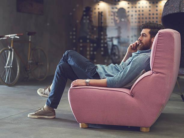 Joven relajante en el sofá y hablando en el teléfono. - foto de stock