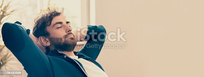 Young man relaxing in his chair in vintage decorated room