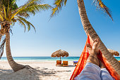 Young man relaxing on a white sand tropical beach. Hanging in a hammock under the palm trees in Tulum, Mexico.