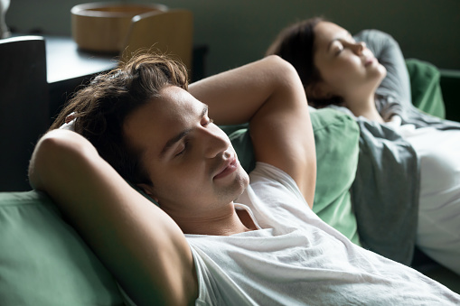 973962076 istock photo Young man relaxing on comfortable couch with girlfriend at home 973962160