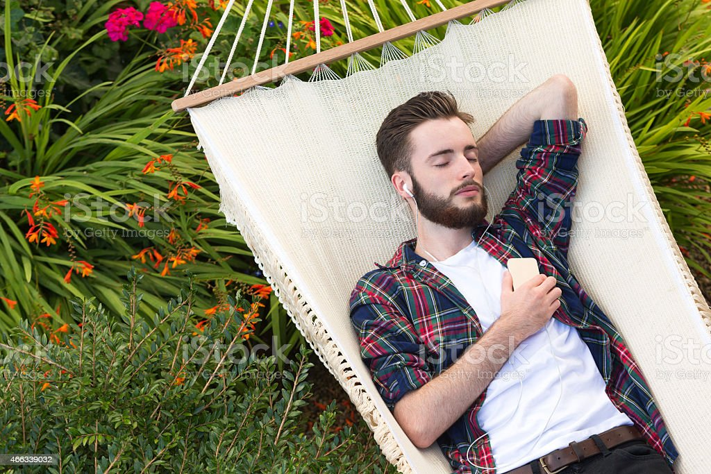 Young Man Relaxing on Hammock Listening to Music stock photo