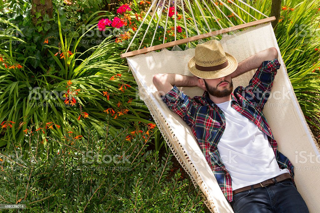 Young Man Relaxing on Hammock Young man having a snooze on a hammock. 20-29 Years Stock Photo