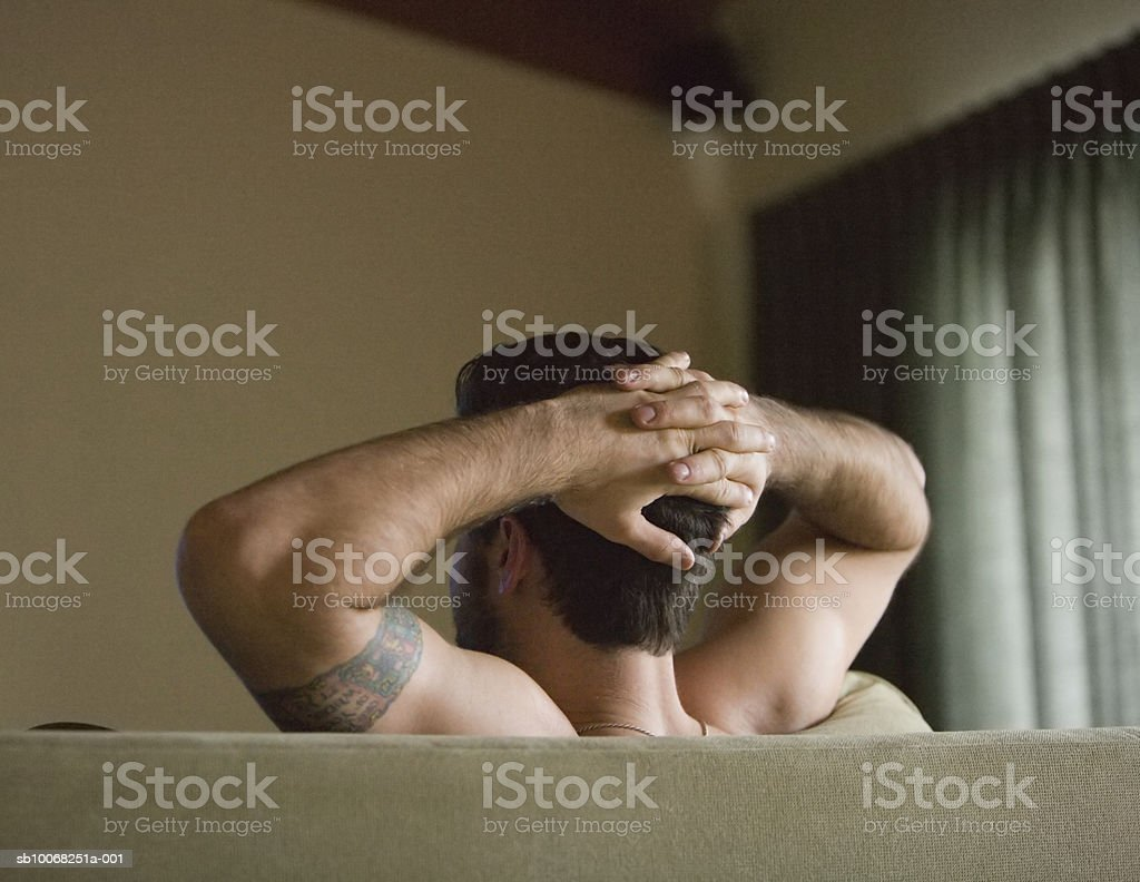 Young man relaxing on sofa with hands on head royalty-free stock photo