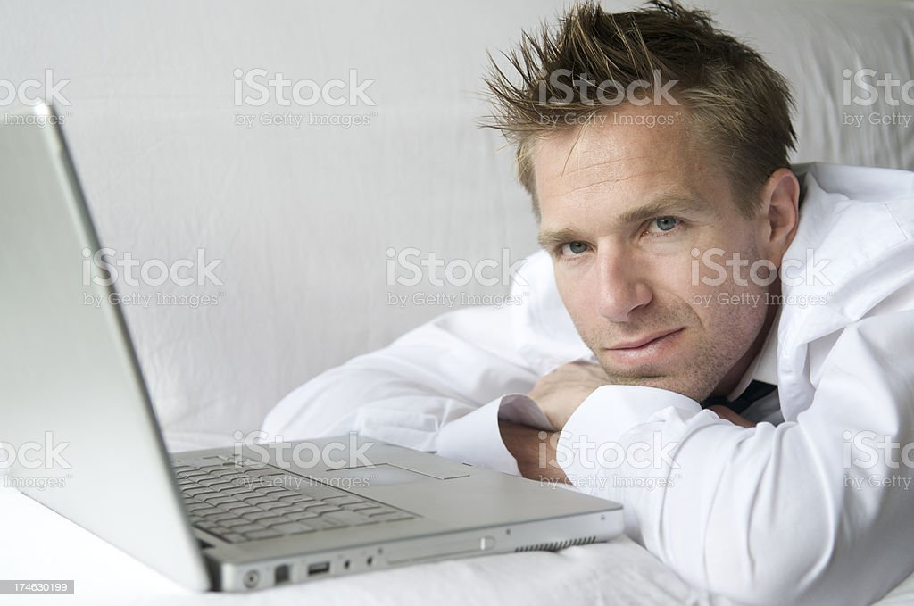 Young Man Relaxing on Sofa with Laptop Computer stock photo