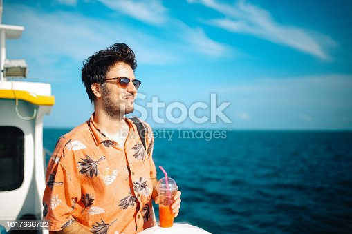 Vintage toned image of a young man enjoying the beautiful summertime on the boat, while traveling from Koh Lanta to Phi Phi islands in Thailand. He is wearing a casual, Hawaiian shirt, having a cold juice to refresh on a hot summertime day in the Indian ocean.